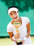 Young female tennis player won the tournament. Successful female tennis player won the cup at the sport competition. Prize Stock Images