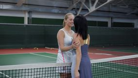Young female tennis players embracing on court after match. Two cheerful sportswomen standing and embracing together on tennis court during the break stock video