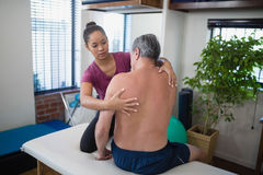 Young female therapist examining back of shirtless senior male patient sitting on bed Stock Photo