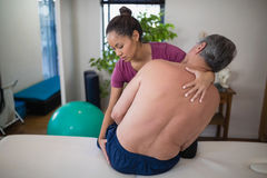 Young female therapist examining buttocks of shirtless senior male patient sitting on bed. At hospital ward royalty free stock photography