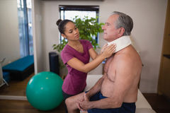Young female therapist examining neck collar on senior male patient. At hospital ward royalty free stock images