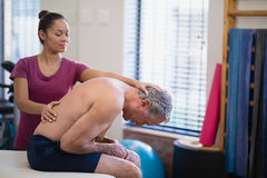 Young female therapist giving back massage to senior male patient bending on bed Royalty Free Stock Photos