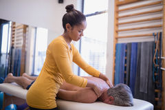 Young female therapist giving neck massage to senior male patient lying on bed Royalty Free Stock Photos