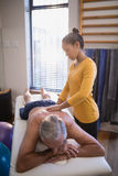 Young female therapist massaging back of senior male patient against window Royalty Free Stock Images