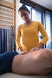 Young female therapist massaging back of senior male patient lying on bed Royalty Free Stock Image