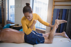 Young female therapist massaging buttocks of senior male patient. At hospital ward Stock Images