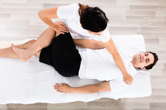 Young Female Therapist Massaging Relaxed Man`s Leg Stock Image