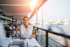 Young female thinking about something good while waiting for her boyfriend in modern open air cafe Stock Images