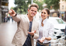 Young female tourist asks for directions from man Stock Photo