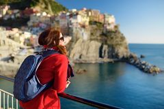 Young female tourist enjoying the view of Manarola, one of the five centuries-old villages of Cinque Terre, located on rugged. Northwest coast of Italian royalty free stock image
