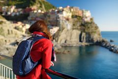 Young female tourist enjoying the view of Manarola, one of the five centuries-old villages of Cinque Terre, located on rugged. Northwest coast of Italian royalty free stock photos