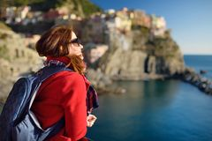 Young female tourist enjoying the view of Manarola, one of the five centuries-old villages of Cinque Terre, located on rugged. Northwest coast of Italian stock images