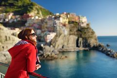Young female tourist enjoying the view of Manarola, one of the five centuries-old villages of Cinque Terre, located on rugged. Northwest coast of Italian royalty free stock photography