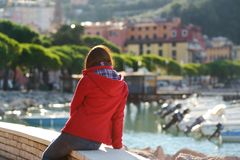 Young female tourist enjoying the view of small yachts and fishing boats in marina of Lerici town, located in the province of La. Spezia in Liguria, Italy stock images