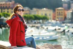 Young female tourist enjoying the view of small yachts and fishing boats in marina of Lerici town, located in the province of La. Spezia in Liguria, Italy royalty free stock photo