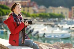 Young female tourist enjoying the view of small yachts and fishing boats in marina of Lerici town, located in the province of La. Spezia in Liguria, Italy royalty free stock photos