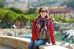 Young female tourist enjoying the view of small yachts and fishing boats in marina of Lerici town, located in the province of La. Spezia in Liguria, Italy royalty free stock image