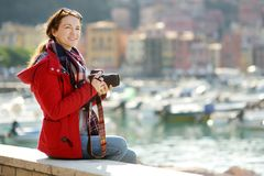 Young female tourist enjoying the view of small yachts and fishing boats in marina of Lerici town, located in the province of La. Spezia in Liguria, Italy stock photo
