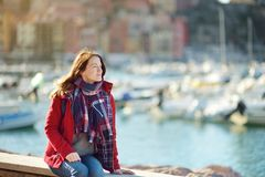 Young female tourist enjoying the view of small yachts and fishing boats in marina of Lerici town, located in the province of La. Spezia in Liguria, Italy stock image