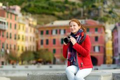 Young female tourist enjoying the view of Vernazza, one of the five centuries-old villages of Cinque Terre, located on rugged. Northwest coast of Italian royalty free stock image
