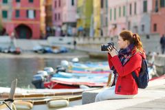 Young female tourist enjoying the view of Vernazza, one of the five centuries-old villages of Cinque Terre, located on rugged. Northwest coast of Italian stock image