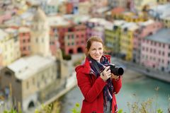 Young female tourist enjoying the view of Vernazza, one of the five centuries-old villages of Cinque Terre, located on rugged. Northwest coast of Italian stock photography