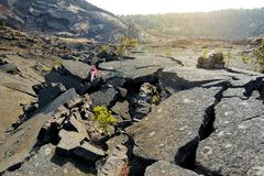Young female tourist exploring surface of the Kilauea Iki volcano crater with crumbling lava rock in Volcanoes National Park in Bi. G Island of Hawaii, USA Stock Photo