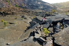 Young female tourist exploring surface of the Kilauea Iki volcano crater with crumbling lava rock in Volcanoes National Park in Bi. G Island of Hawaii, USA Stock Photography