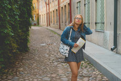 Young female tourist get lost in old town. Young female tourist with map get lost on narrow street of scenic european old town royalty free stock images