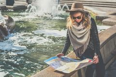 Young female tourist in hat and sunglasses is sitting on street of European city near fountain,holding destination map. Girl is traveler looking for way on map Royalty Free Stock Photo