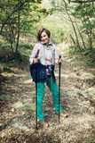 Young female tourist with hiking poles in autumn outdoors Stock Image