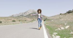 Young female tourist hitch hiking. Young woman in casual outfit standing on road with backpack and hitch hiking on of mountains stock video footage