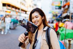Young female tourist holding a gimbal with smartphone and recording videos. Travel blogger and vlogger concept. Young Asian female tourist woman holding a gimbal royalty free stock photos