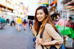 Young female tourist holding a gimbal with smartphone and recording videos. Travel blogger and vlogger concept. Young Asian female tourist woman holding a gimbal stock photography