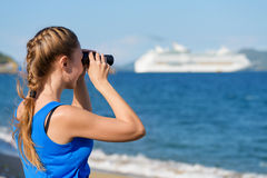 Young female tourist looking through binoculars at cruise liner Stock Photography
