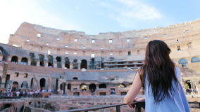 Young female tourist looking at the Colosseum inside in Rome, Italy. The Colosseum is the main tourist attractions of. Happy tourist in Rome over Colosseum stock video footage