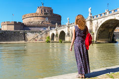 Young female tourist looks at the Castel Sant`Angelo in Rome Royalty Free Stock Images