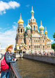 Young female tourist near the Church of Savior on Spilled Blood. Young female tourist on the background of Church of the Savior on Spilled Blood in Saint royalty free stock image