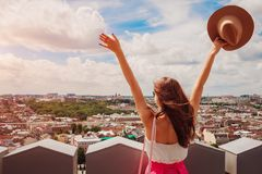 Young female tourist with raised hands looking on Lviv, Ukraine from viewpoint. Happy traveller. Vacation concept royalty free stock image