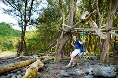 Young female tourist relaxing on a handmade swing on rocky beach of Pololu Valley on Big Island of Hawaii. USA Royalty Free Stock Photography