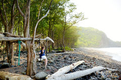 Young female tourist relaxing on a handmade swing on rocky beach of Pololu Valley on Big Island of Hawaii Stock Image