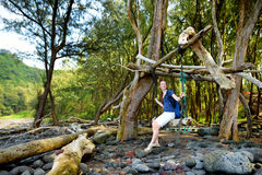 Young female tourist relaxing on a handmade swing on rocky beach of Pololu Valley on Big Island of Hawaii Royalty Free Stock Photo