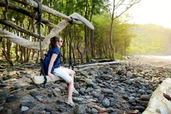 Young female tourist relaxing on a handmade swing on rocky beach of Pololu Valley on Big Island of Hawaii. USA Stock Photo