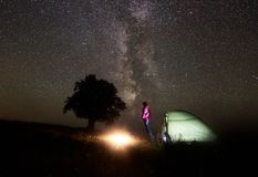 Young female tourist resting near illuminated tent, camping in mountains at night under starry sky. Night camping in mountains. Hiker woman standing near stock photo