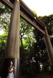 A young female tourist resting under the big torii placed in one of the entrances of Meiji-Jingu temple in Tokyo.  Royalty Free Stock Photo