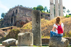 Young female tourist rests on the ruins of the Roman Forum in Ro Stock Images