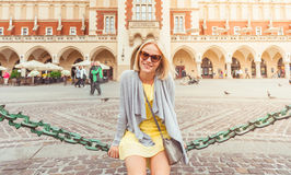 Young female tourist sitting near Cloth Hall in the old city center of Krakow Stock Image