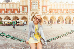 Young female tourist sitting near Cloth Hall in the old city center of Krakow Stock Photos