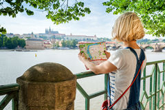Young female tourist studying a map of Prague. Pretty young female tourist studying a map against the background of the old town and the Vltava River in Prague royalty free stock photos