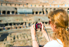 Young female tourist takes a picture inside the Coliseum in Rome Stock Image